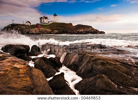 A view of the Cape Neddick lighthouse across the rocks showing the waves.