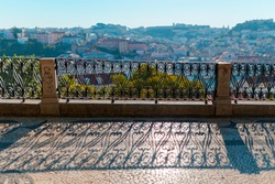 A view of the city through the grille of a black metal fence. A view of the roofs of the houses from a bird's-eye view. Lisabon. Portugal.