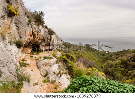 A view of the famous, ancient Euripides cave and the sea on a cloudy spring day (island Salamis, Greece). #1039278379