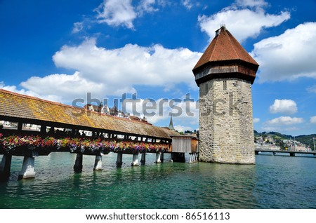 A view of the famous wooden Chapel Bridge of Luzern in Switzerland, with the tower in foreground