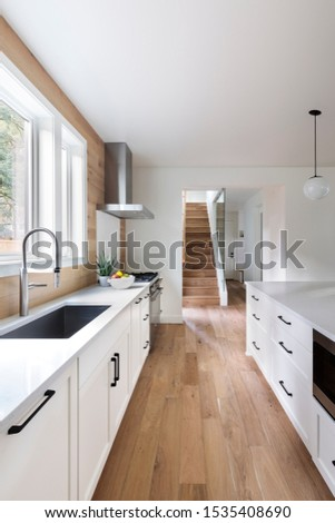 A view of the galley style kitchen with windows filtering the sunlight. Lake Oswego, Oregon. Stockfoto ©