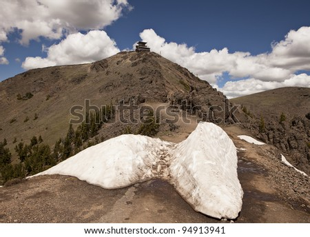 A view of the hiking trail leading to the summit of Mt. Washburn in Yellowstone National Park and the lookout station on the peak used by park rangers to look for forest fires.