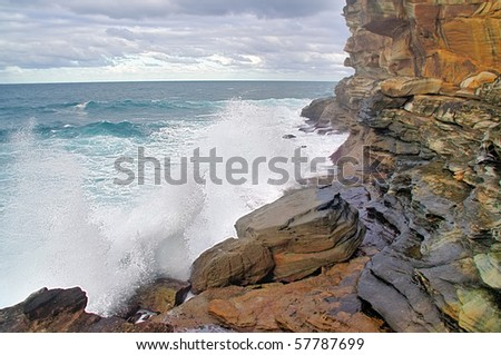 A view of the huge surf crashing on the red cliffs around famous Bondi, Bronte and Tamarama beach, Australia