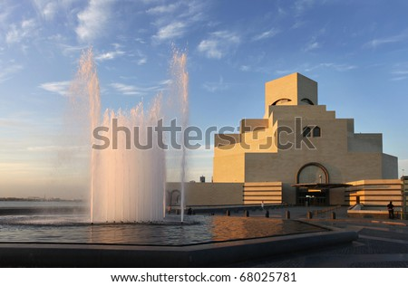 A view of the imposing Museum of Islamic Art in Doha, Qatar, Arabia under a cloudy winter sky, with the water catching the evening sun.
