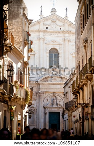 A view of the main street in Lecce with the crowds promenading in the late afternoon sun. The church of St Irene, built from 1591 by Francesco Grimaldi, provides the backdrop.