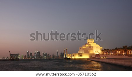A view of the Museum of Islamic Art at night, with the Dafna district's high-rise skyline in the background.