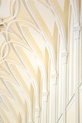A view of The neo-gothic ceiling and pillars of the catholic church. Colonnade in the interior of a church. The gothic geometric arch ceiling.