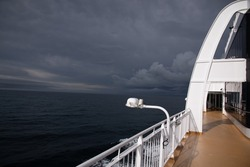 A view of the open, deep blue sea from the railing of a passenger ship - in the background you can see how a storm or thunderstorm is formed on the sea - dark, black clouds on the open sea