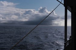 A view of the open, deep blue sea from the railing of a passenger ship - in the background you can see how a storm or thunderstorm is formed on the sea - dark, black clouds  - steel rope