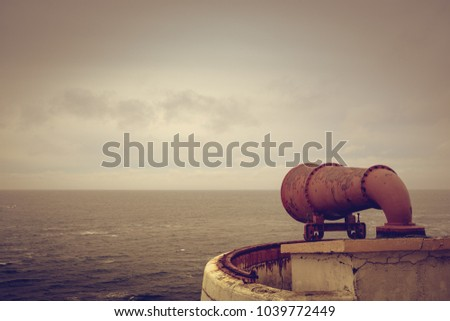 A view of the open ocean in the foreground with a rusty siren, in retro style. - Shutterstock ID 1039772449