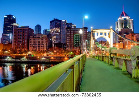 A view of the Pittsburgh, Pennsylvania cityscape at night from the Roberto Clemente Bridge overlooking the Allegheny River.