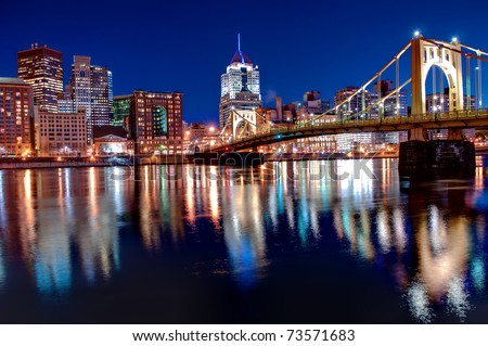 A view of the Pittsburgh, Pennsylvania cityscape at night overlooking the Allegheny River with views of the Roberto Clemente Bridge.