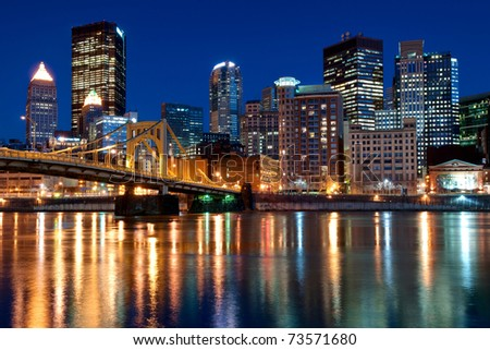 A view of the Pittsburgh, Pennsylvania cityscape at night overlooking the Allegheny River with a view of the Andy Warhol Bridge.