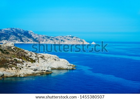 a view of the Punta San Francesco promontory in Calvi, Corse, surrounded by the Mediterranean sea, and the Punta Revellata promontory in the background, highlighting its lighthouse on the right #1455380507
