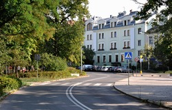 A view of the road with a bend in the distance, an old renovated tenement house