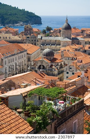 A view of the roofs of Dubrovnik with an emphasis on a rooftop garden, the cathedral and the St-Blaise church
