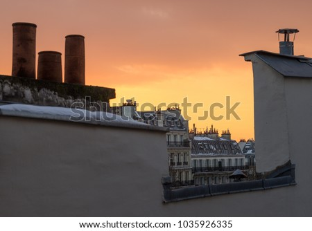 A view of the rooftops of Paris under the snow, at sunset.