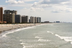 A view of the shore at North Myrtle Beach South Carolina. People are strolling the beach in front of the motels.
