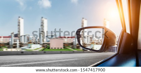 A view of the steel plant reflected from the side rearview mirror of the vehicle as the vehicle travels on a road outside the steel plant. #1547417900