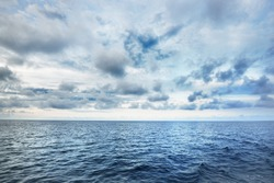A view of the stormy North sea from a sailing boat. Cloudy blue sky reflecting in the water. Dramatic cloudscape. Rogaland region, Norway. Leisure activity, environmental conservation concepts