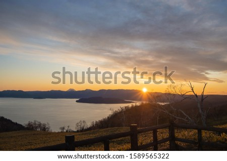 A view of the sunset over the mountains over the lake.