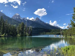 A view of the tetons from the clear bluish-greenish waters of taggart lake