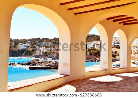 a view of the the Barques Beach and the coast of Calella de Palafrugell, in the Costa Brava, Catalonia, Spain, seen through the arches of the characteristics porticos of its white houses #629336603