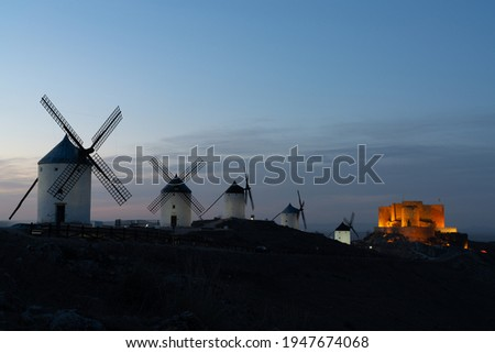 A view of the windmills and castle of Consuegra in La Mancha in central Spain at sunset Foto stock ©