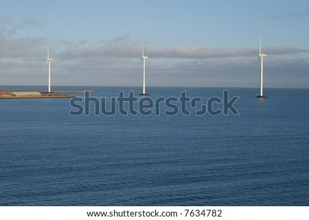 A view of three tall wind-powered electricity generators built just offshore in Frederikshavn, Denmark.