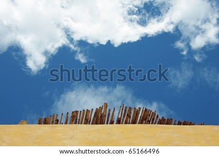 a view on a blue sky and a part of beach parasol suggesting holidays and evasion