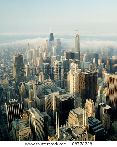 A view on a day with Clouds rolling over Chicago city downtown Skyline with aerial view of  buildings covered partially with clouds