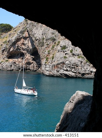 A view on an anchoring sailboat through a window in a cave...