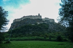 A view on Riegersburg castle in Austria. The massive fortress was build on the rock, towering above the landscape. Lush meadow underneath. Clear, blue sky above. Middle ages. Defensive structure