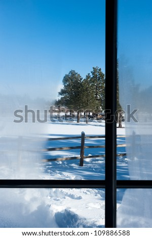 A view out a cabin window with condensation overlooking a snowy mountain landscape - stock photo