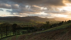 A view over a lake district valley at late afternoon in autumn with light hitting the landscape between the clouds. The sun i very bright and contrasts with the dark clouds in the image.