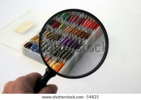 a view through a magnifying glass of many colors of embrordarythread lined up in its  box on a white background