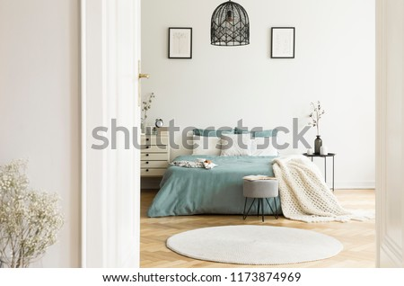 A view through an open door into a sunny bedroom interior with sage color linen and cushions on a bed, blanket, drawer cabinet, soft stool and a round rug. Real photo