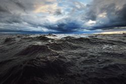 A view to the North sea from a sailing boat at sunset. Dramatic stormy sky, sun rays through the dark clouds. Epic seascape. Deep cyclone in winter. Norway. Concept image, climate change,  ecology