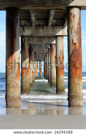 A view under a long, tall pier and the rusted pilings supporting it.  Taken in the late afternoon sun with deep shadows.
