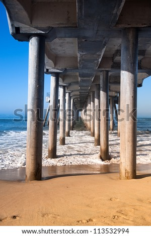 A view underneath a pier showing the pilings that support this massive structure.