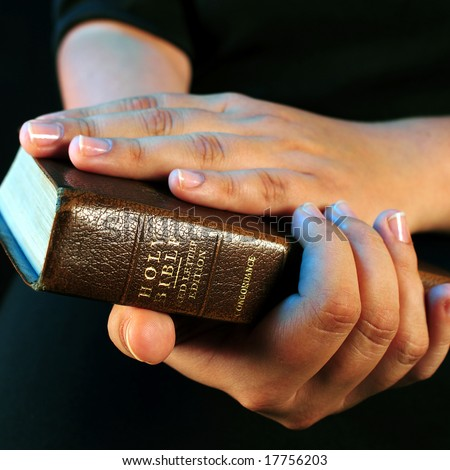 A view with a bible and praying hands