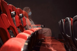 A viewer in a medical mask watching a movie in an empty cinema hall, transparent concept. Problems with cinema tickets during the coronavirus pandemic