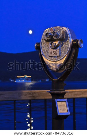 A viewfinder on a dock on Lake George with a full moon and paddle wheel ferry in the background in the Adirondack State Park in New York.
