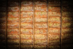 A vignette photo of a rustic, weathered wooden wall covered with peeling orange and yellow paint.
