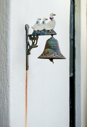 A vintage / antique door bell design mounted on the wall of a traditional old farm house. It is styled with a row of ducks and has started to rust.