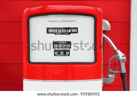 A vintage antique Gasoline fuel pump on red background