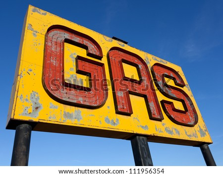 A vintage, antique, gasoline sign in front of a blue sky on  a sunny day - stock photo