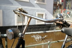 A vintage bicycle leaned on a metal railing along a city stream in Freiburg in Germany called Baechle. It the stream on the background there is a skeleton of an old damage bicycle out of service.