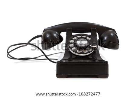 A vintage, black 1940's telephone on a white background