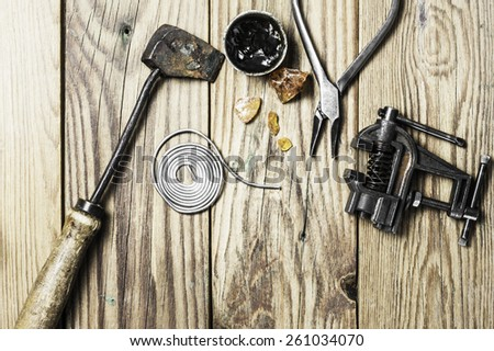A vintage brazing copper  iron, a solid tin wire, some colophony, a grip vice and pliers on a wooden background #261034070